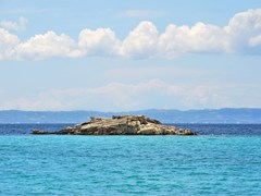 Kalogria beach, Small rocky island near in Sithonia, Chalkidiki, Greece, with a view on Kassandra peninsula.