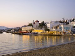 08_Sunset-on-the-sea-near-the-island-of-Mykonos-in-Greece-and-the-night-lights-of-restaurants-and-churches-on-the-beach-...